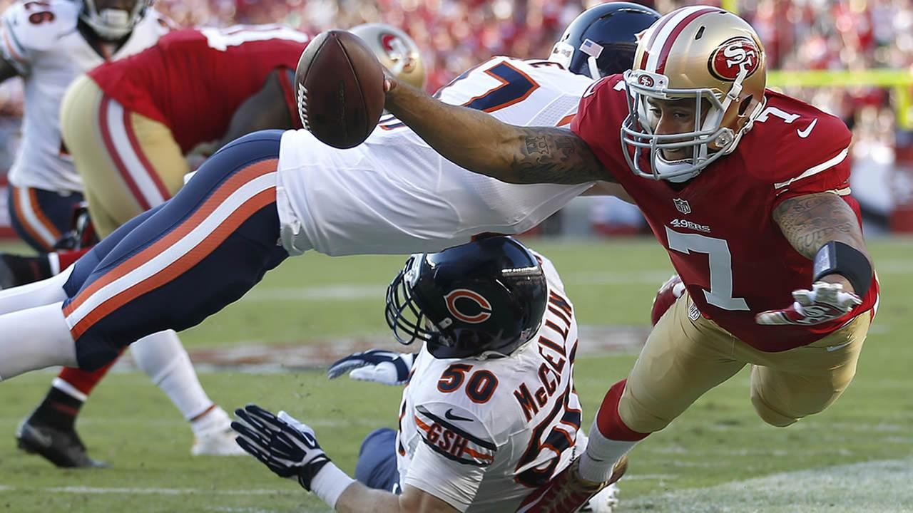 San Francisco 49ers quarterback Colin Kaepernick (7) is pushed out of bounds by Chicago Bears free safety Chris Conte, top, as Shea McClellin helps on defense during the first quarter of an NFL football game in Santa Clara, Calif., Sunday, Sept. 14, 2014.