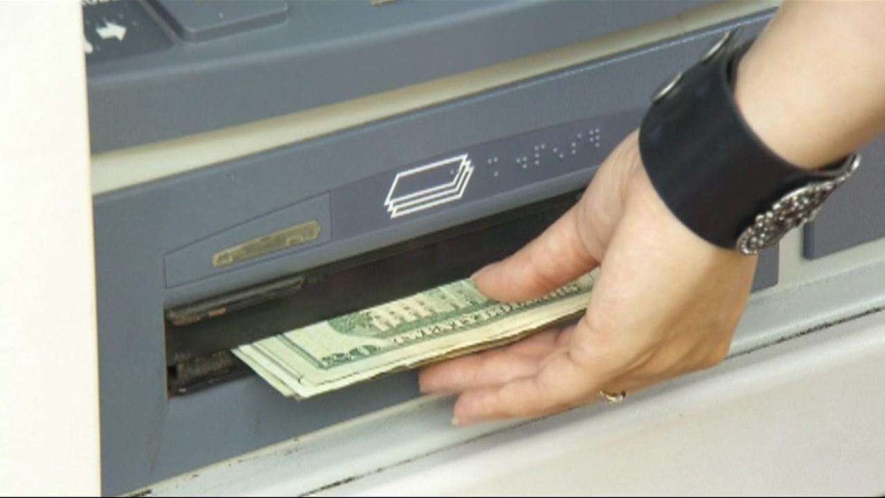 A hand grabs money from an ATM in this undated file photo.
