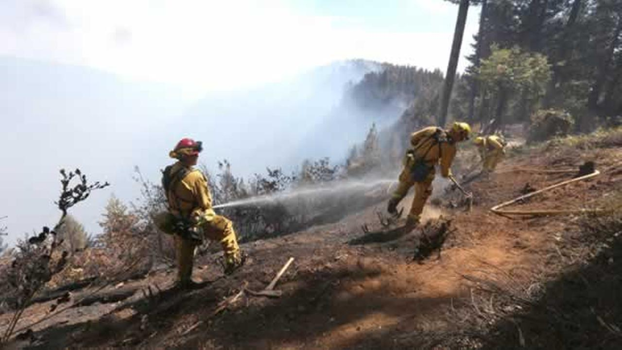 Firefighters hose down hot spots of the King Fire near Pollack Pines, Calif., Monday, Sept. 15, 2014.