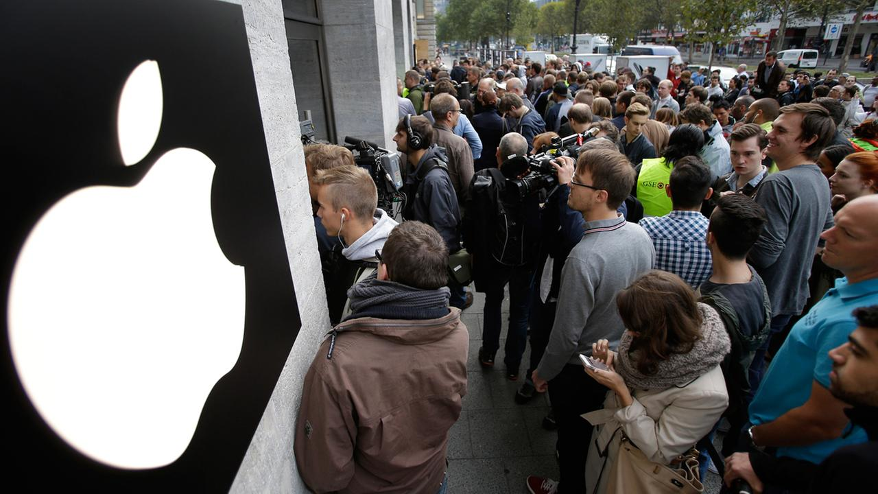 People queue in front of the Apple store to buy the new iPhone in Berlin, Germany, Friday, Sept. 19, 2014. (AP Photo/Michael Sohn)