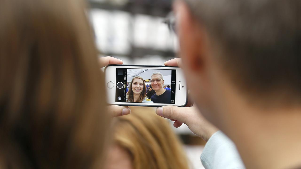 Tim Cook, CEO of Apple Inc., takes a photograph with Apple employee