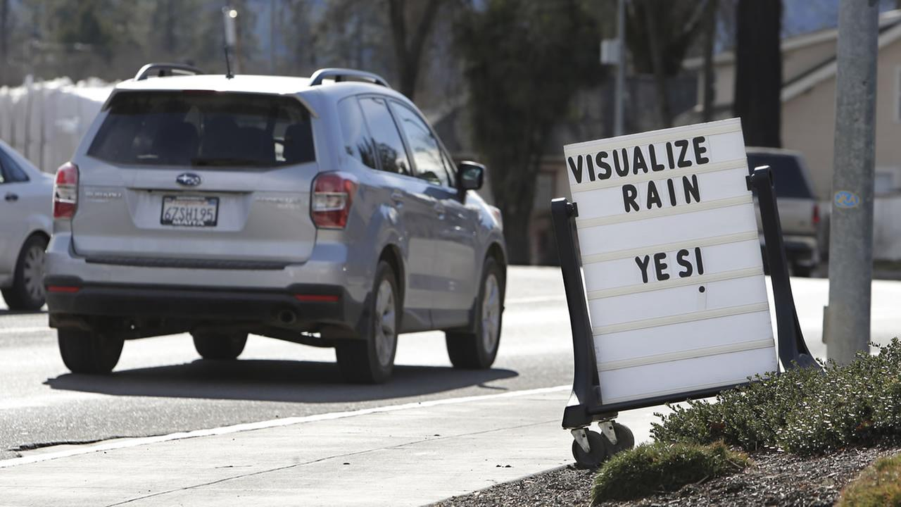 Cars drive past a sign outside of a market reminding residents about the short water supply in Willits, Calif.