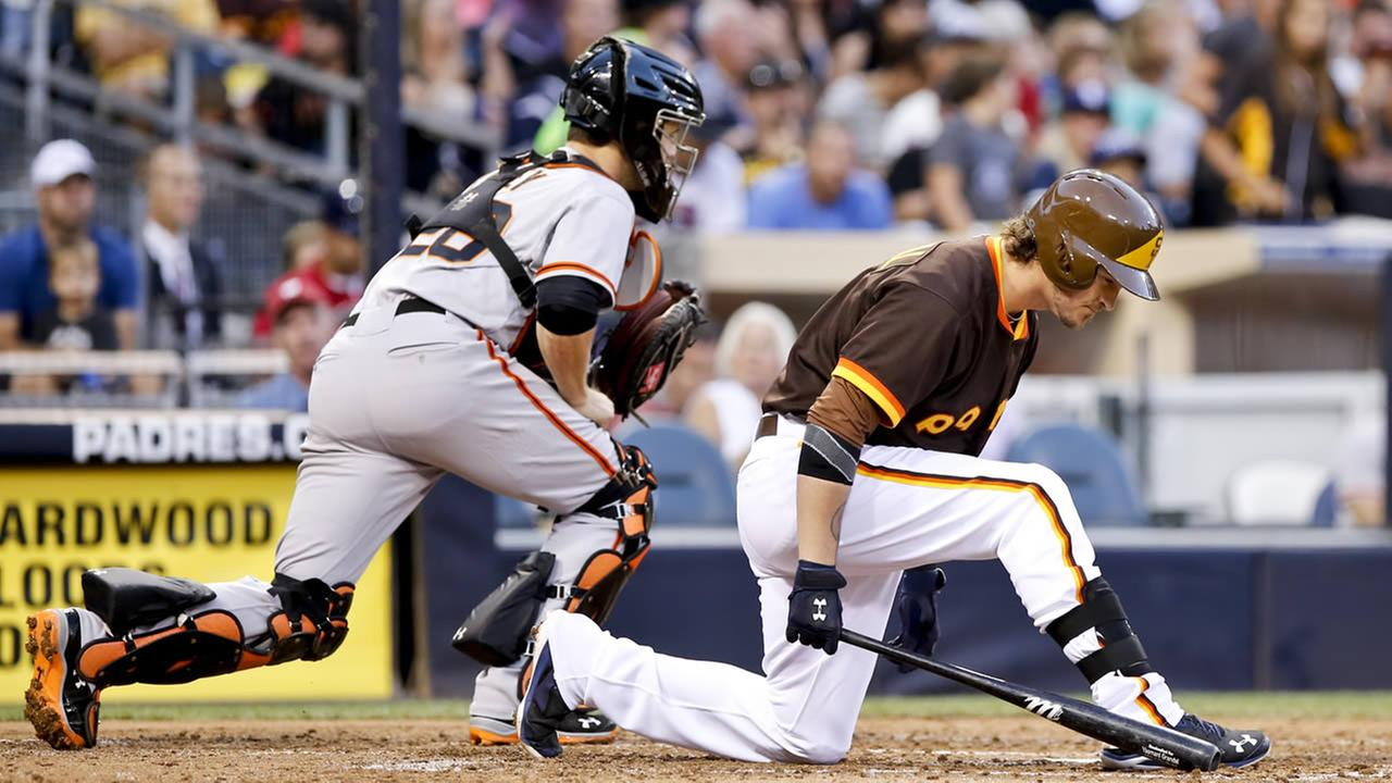 Padres Yasmani Grandal reacts to striking out with bases loaded against the Giants during the third inning of a baseball game Saturday, Sept. 20, 2014, in San Diego. Giants catcher Buster Posey heads to the dugout (AP Photo/Don Boomer)