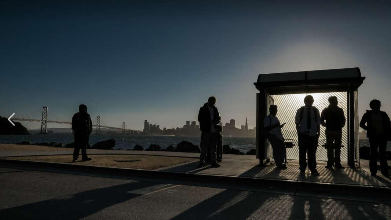 People are seen waiting at a bus stop on Treasure Island on Wednesday, March 7, 2018.