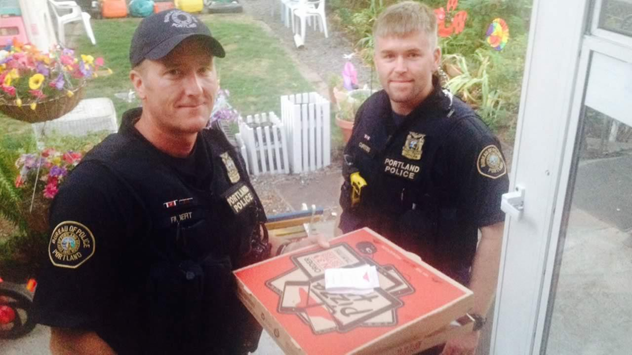 n this photo taken Sept. 1, 2014, two police officers pose after completing a pizza delivery after a Pizza Hut delivery driver was hurt in a crash in Portland, Ore.  (AP Photo/Steve Huckins)