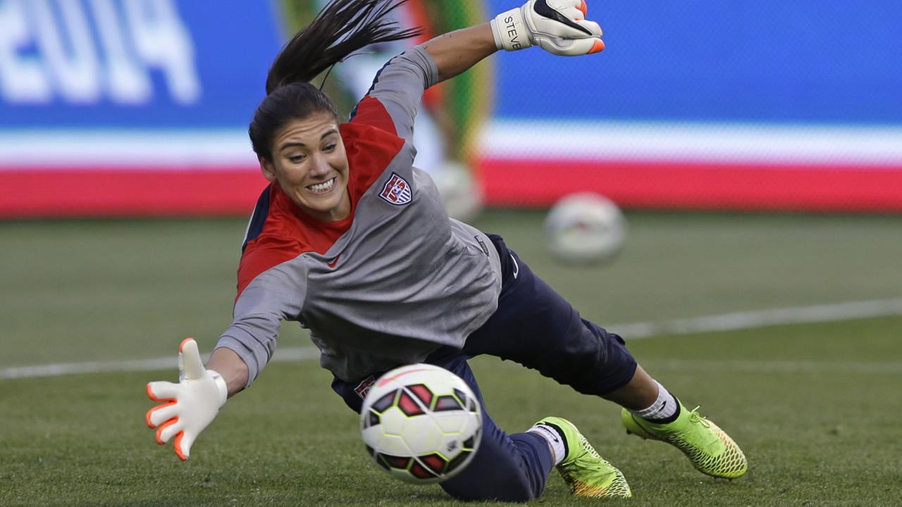 U.S. goalkeeper Hope Solo dives for a ball during practice before an international friendly game with Mexico on Saturday, Sept. 13, 2014, in Sandy, Utah.(AP Photo/Rick Bowmer)