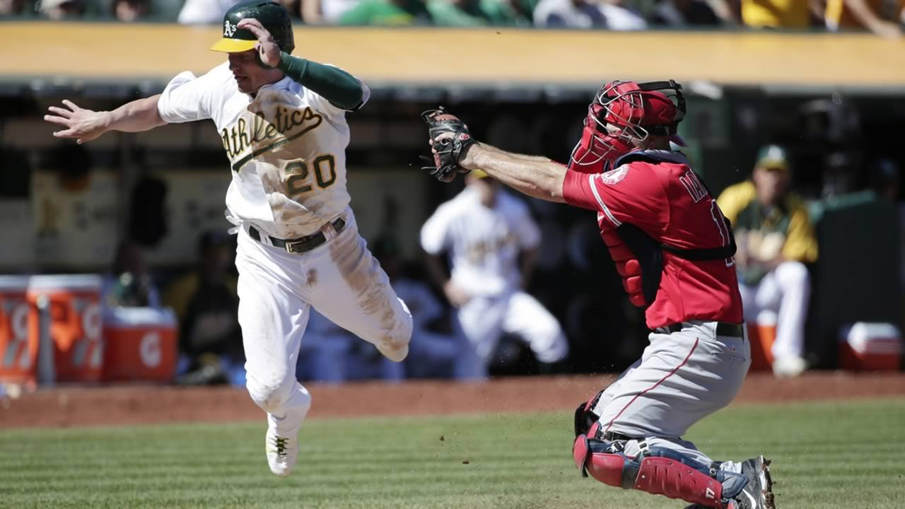 Oakland Athletics Josh Donaldson, left, is tagged out at the plate by Los Angeles Angels catcher Chris Iannetta during a game on Sept. 24, 2014, in Oakland, Calif. (AP Photo/Marcio Jose Sanchez)