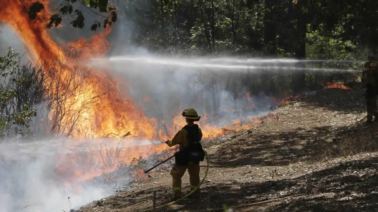 Firefighters hold the line with water hoses during a controlled burn while fighting the King Fire.