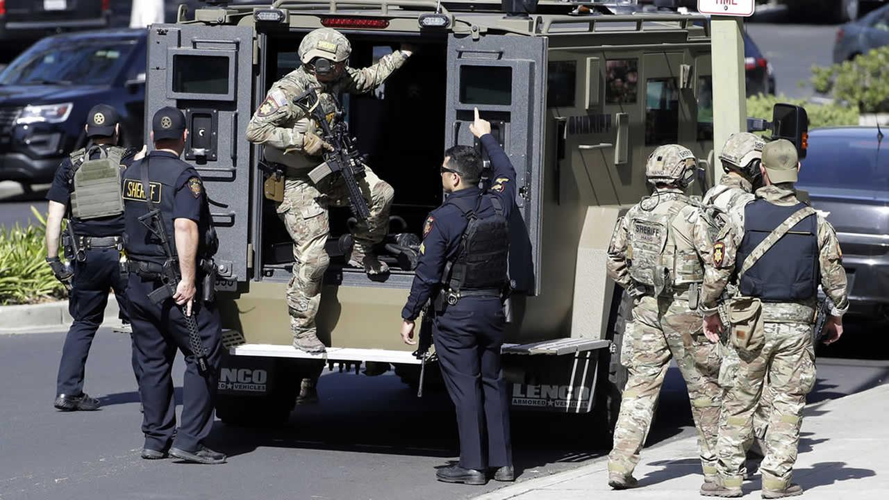 Armed law enforcement personnel exit an armored vehicle outside YouTube headquarters, Tuesday, April 3, 2018, in San Bruno, Calif.