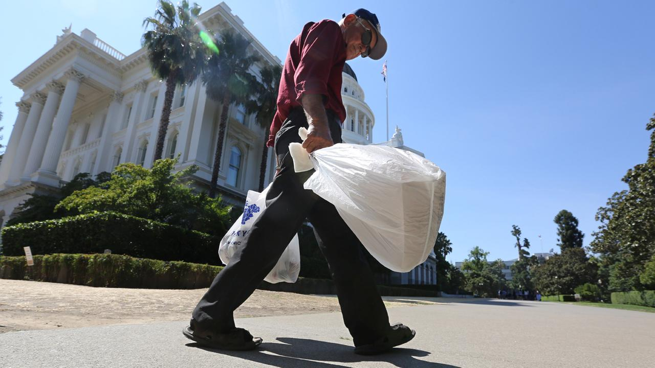 In this photo taken Tuesday, Aug. 12, 2014, plastic single-use bags are carried past the State Capitol in Sacramento, Calif.