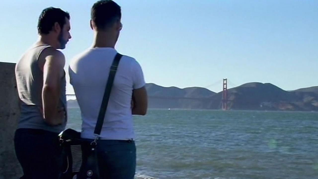 Two men look at the bay and Golden Gate Bridge on a clear day