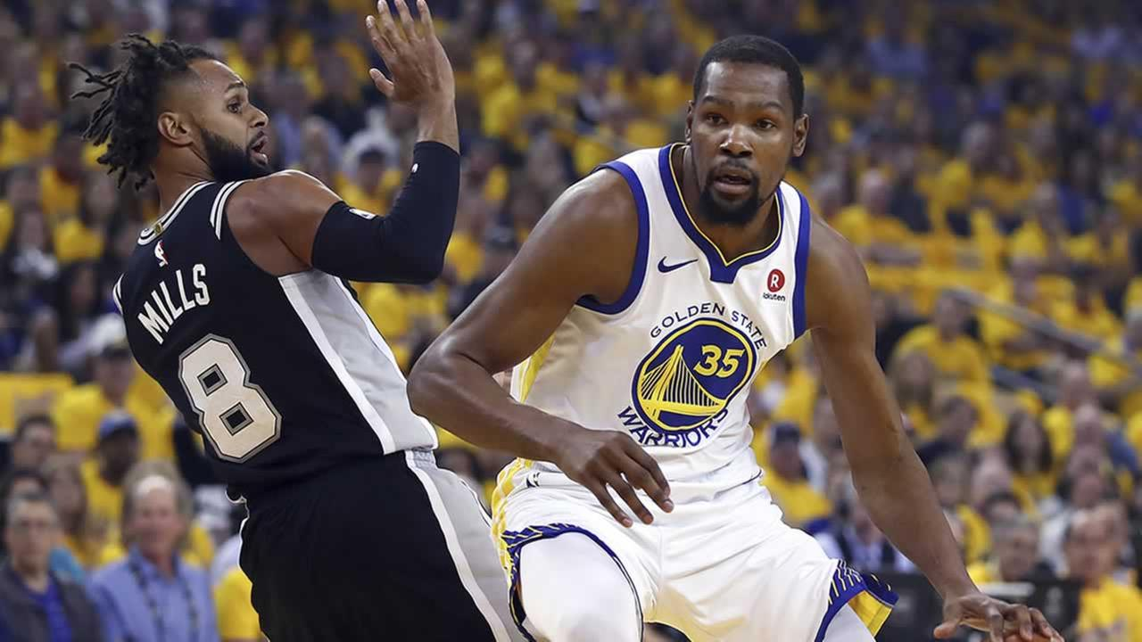 Golden State Warriors Kevin Durant drives the ball around San Antonio Spurs Patty Mills during Game 1 of the NBA playoff series Saturday, April 14, 2018, in Oakland, Calif.