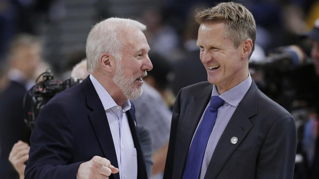 San Antonio Spurs coach Gregg Popovich, left, jokes with Golden State Warriors coach Steve Kerr before an NBA basketball game Tuesday, Nov. 11, 2014, in Oakland, Calif.