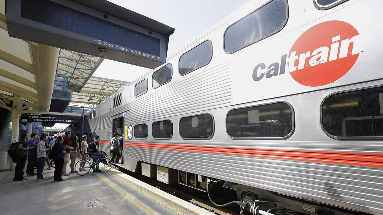 Commuters board a Caltrain train at the Caltrain and Bay Area Rapid Transit station in Millbrae, Calif., Monday, July 1, 2013. (AP Photo/Jeff Chiu)