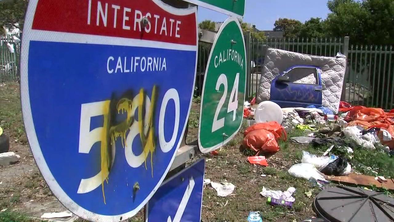 Illegally dumped trash and waste is seen near a highway sign in Oakland, Calif. in this undated image.