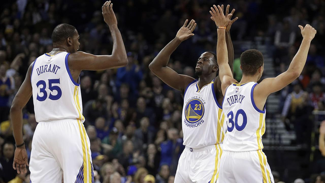 Golden State Warriors Draymond Green celebrates a score against the Houston Rockets with Kevin Durant and Stephen Curry during a game on Dec. 1, 2016, in Oakland, Calif. (AP Photo/Ben Margot)