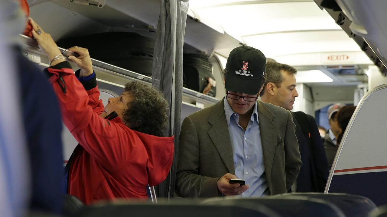 A passenger checks his cell phone while boarding a flight. (AP Photo/Matt Slocum)