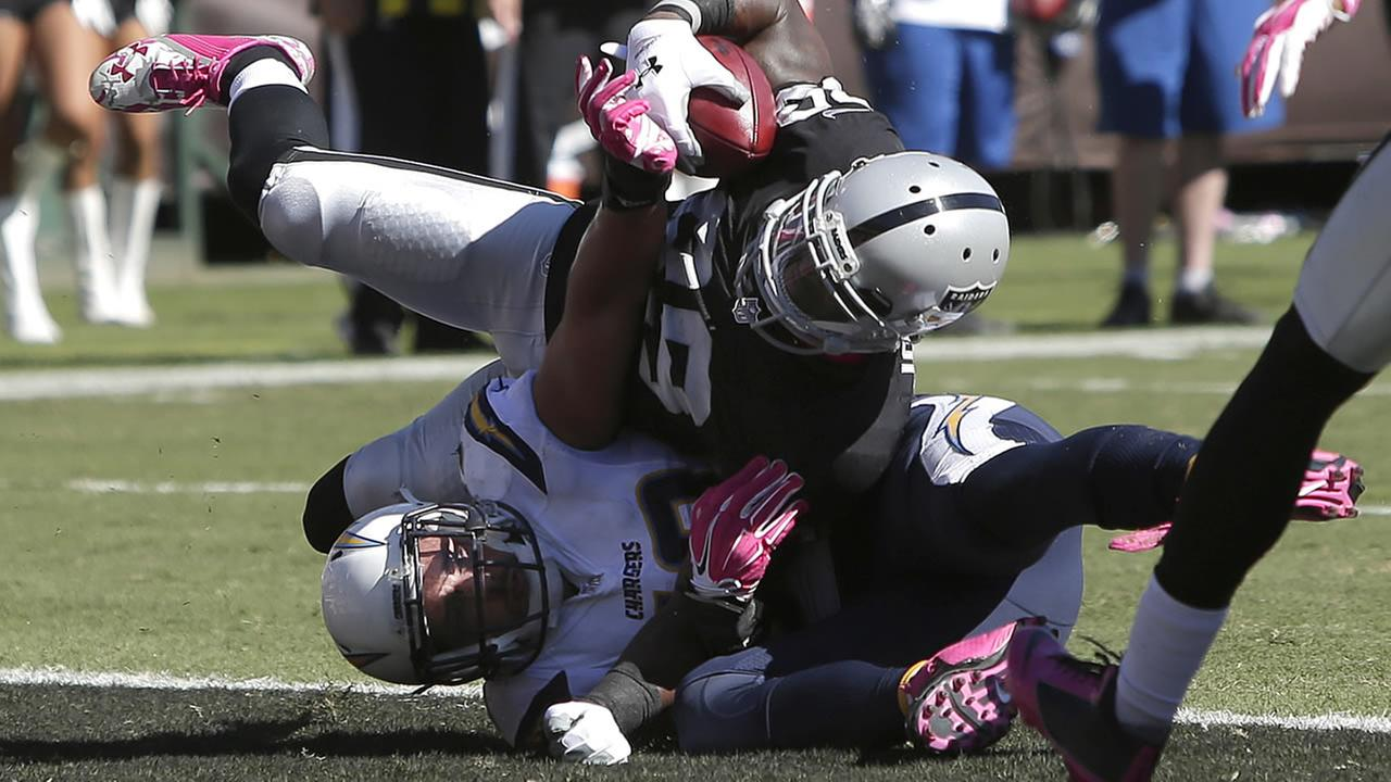 Raiders James Jones, top, scores on a 6-yard touchdown reception over Chargers Andrew Gachkar during a game in Oakland, Calif., on Oct. 12, 2014. (AP Photo/Marcio Jose Sanchez)