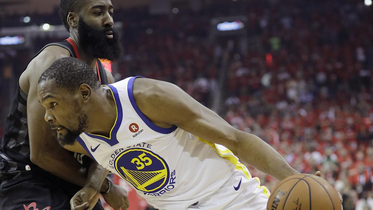 Warriors forward Kevin Durant (35) drives around Rockets guard James Harden, left, during Game 2 of the NBA Western Conference Finals, Wednesday, May 16, 2018, in Houston.