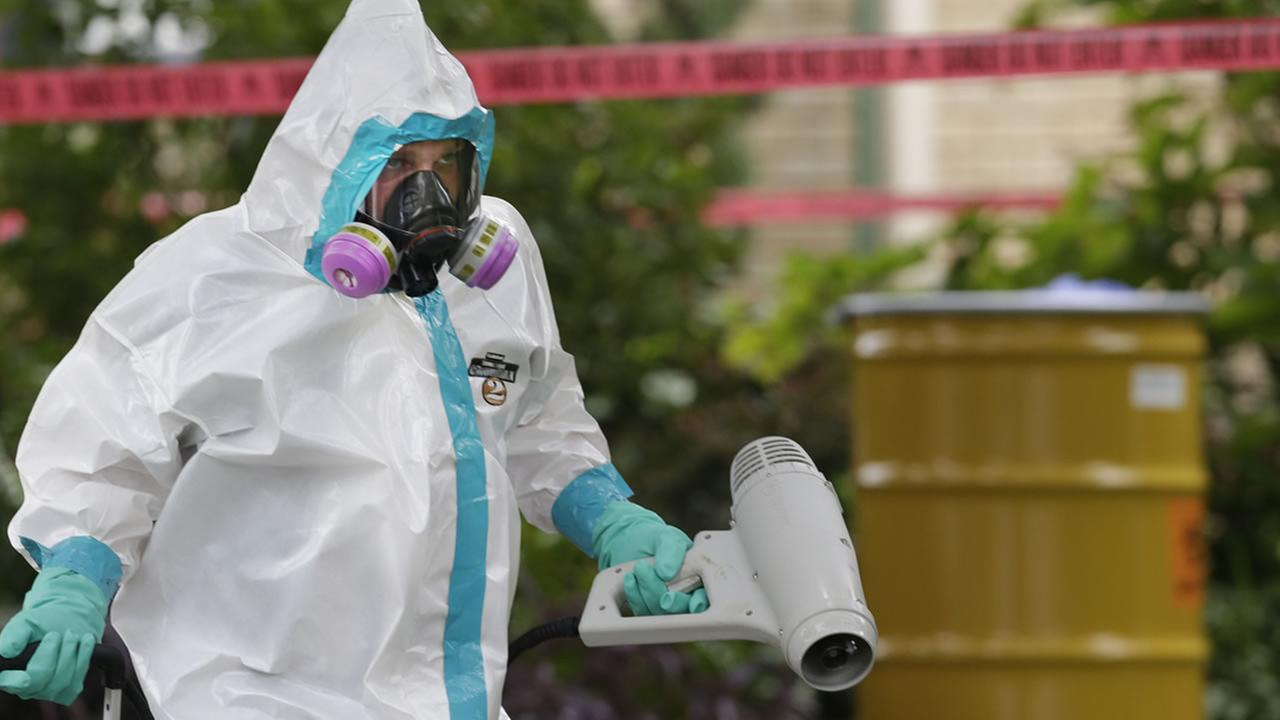A hazmat worker clean outside the apartment building of a hospital worker, Sunday, Oct. 12, 2014, in Dallas. (AP Photo/LM Otero)