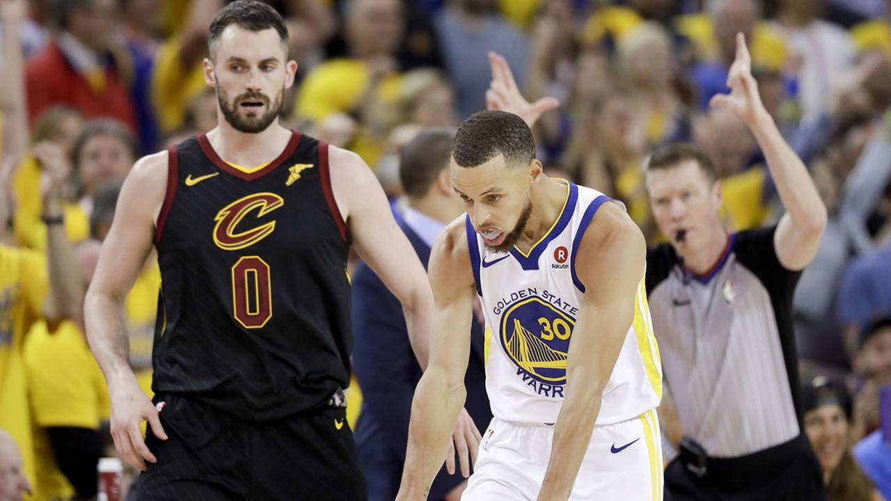 Golden State Warriors guard Stephen Curry celebrates in front of Cleveland Cavaliers forward Kevin Love (0) during the second half of Game 1 of basketballs NBA Finals in Oakland, Calif., Thursday, May 31, 2018. (AP Photo/Marcio Jose Sanchez)