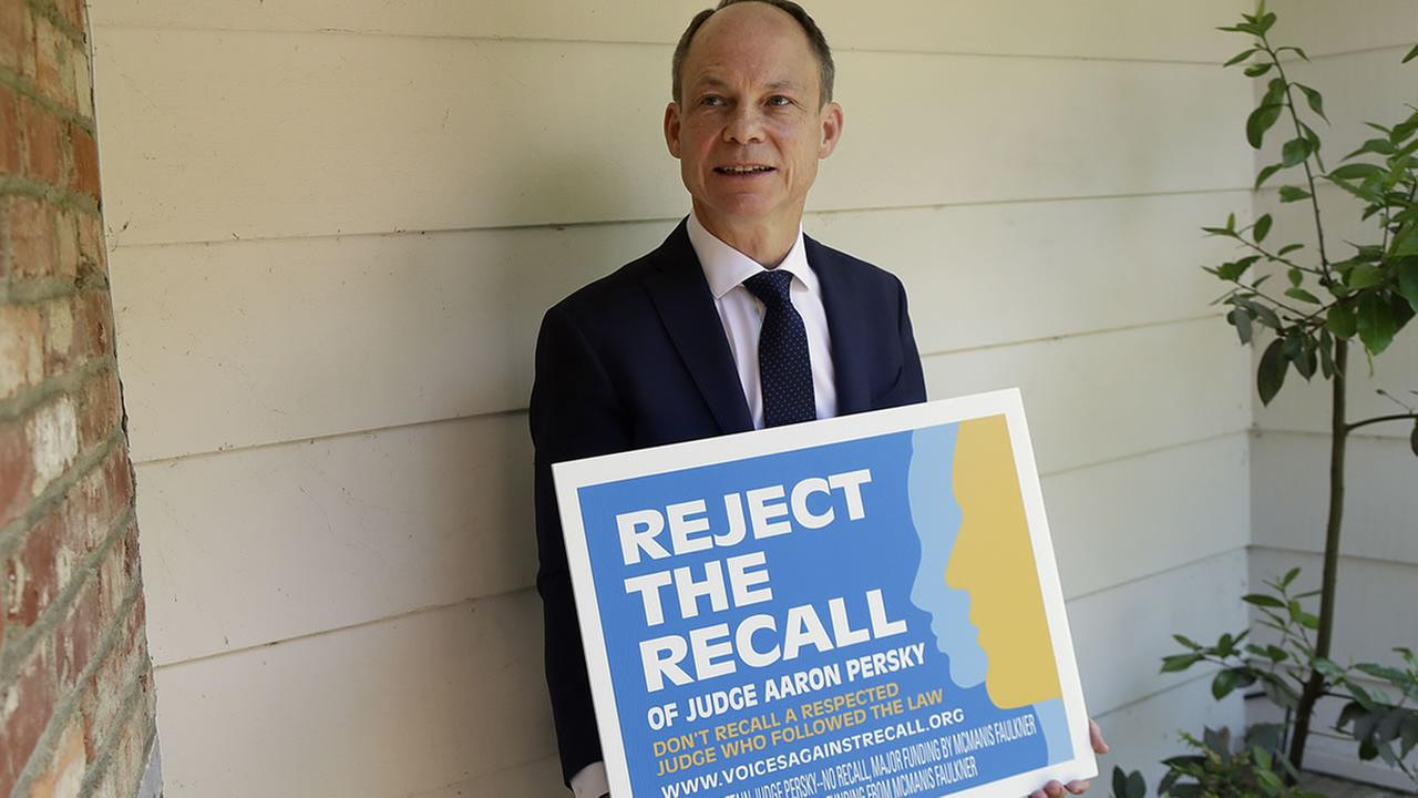 In this May 15, 2018 file photo, Judge Aaron Persky poses for a photo with a sign opposing his recall in Los Altos Hills, Calif.