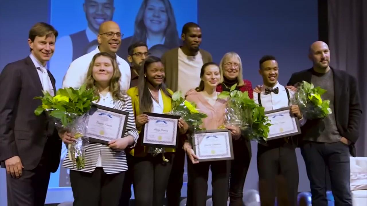 Warriors star Kevin Durant takes a photograph with the four students hes helping by paying for their first year of college.