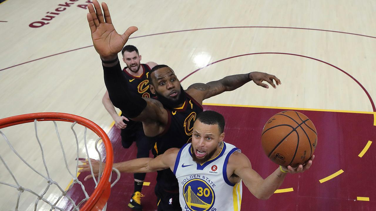 Golden State Warriors Stephen Curry shoots next to Cleveland Cavs LeBron James during the second half of Game 3 of basketballs NBA Finals, Wednesday, June 6, 2018, in Cleveland.