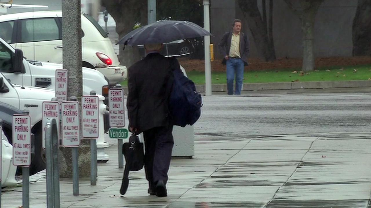 Man walking with umbrella in the rain.