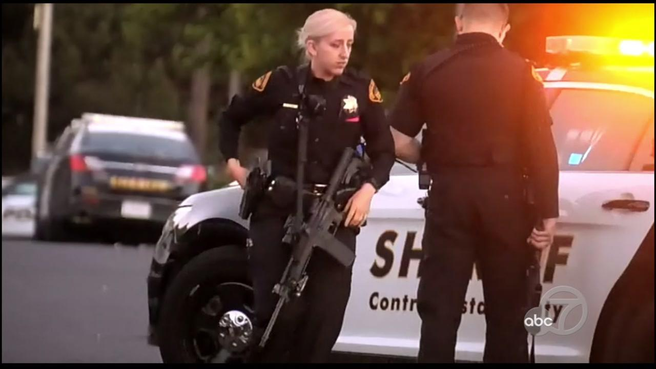 Police armed with assault rifles stand outside of an El Sobrate, Calif. home on Sunday, June 10, 2018.