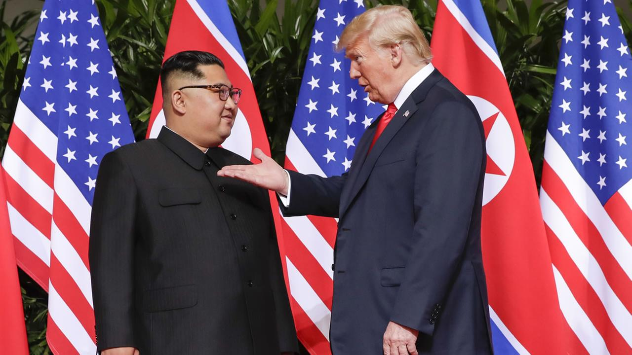 U.S. President Donald Trump reaches to shake hands with North Korea leader Kim Jong Un at the Capella resort on Sentosa Island Tuesday, June 12, 2018 in Singapore.