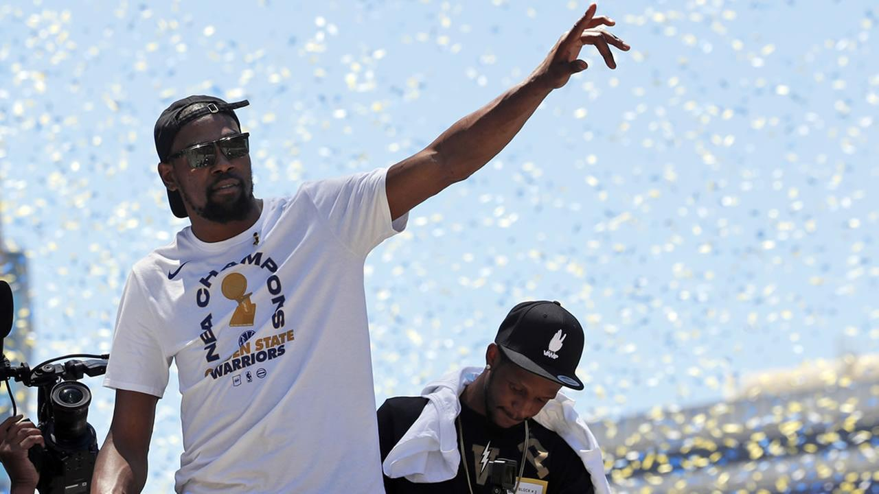 Warriors Kevin Durant waves to fans during the teams NBA basketball championship parade, Tuesday, June 12, 2018, in Oakland, Calif.