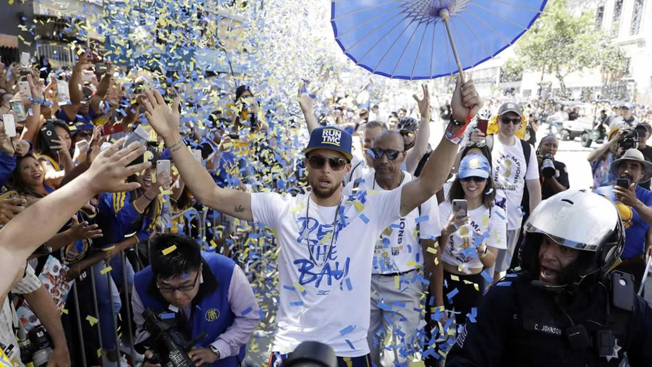 Warriors Stephen Curry celebrates with fans during a parade after winning the NBA basketball championship Tuesday, June 12, 2018, in Oakland, Calif.