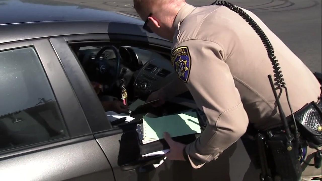 A California Highway Patrol officer is seen issuing a citation to a driver in San Jose, Calif. on Monday, June 18, 2018.