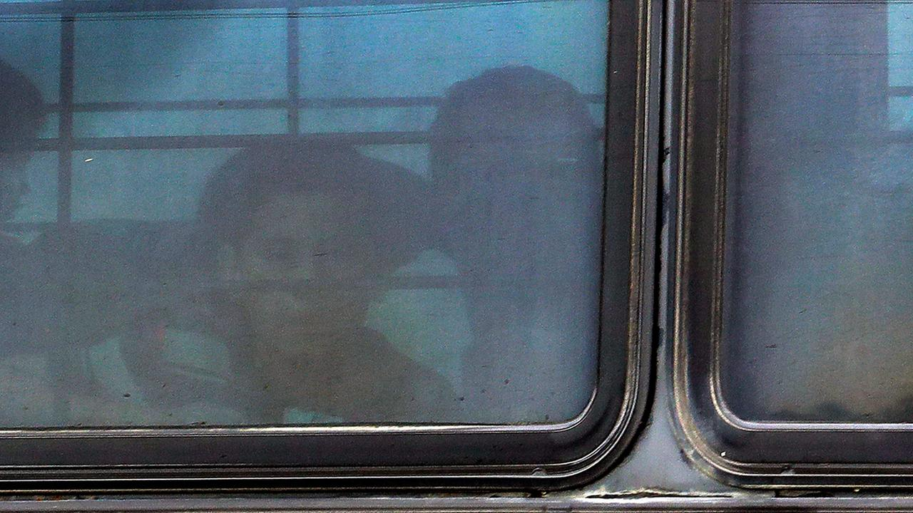 A boy stares out of a heavily tinted bus window leaving a U.S. Customs and Border Protection facility, Tuesday, June 19, 2018, in McAllen, Texas.