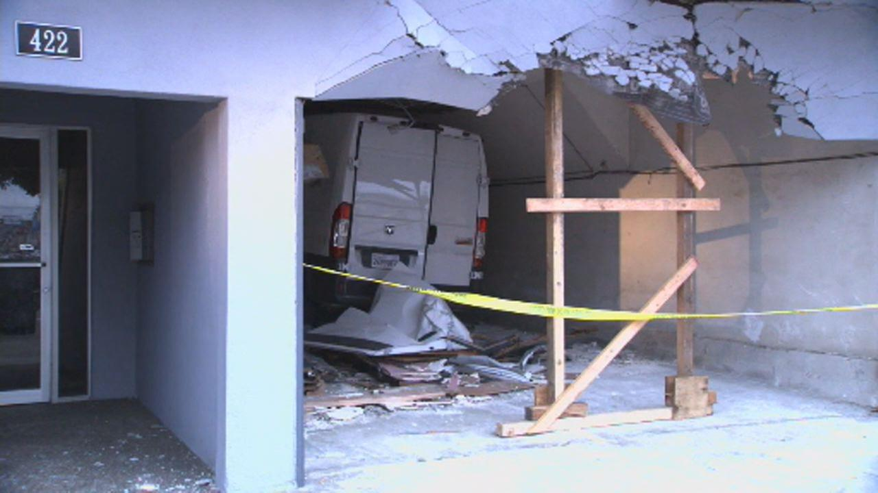 This image shows a white van after it crashed into a San Francisco apartment building on June 20, 2018.