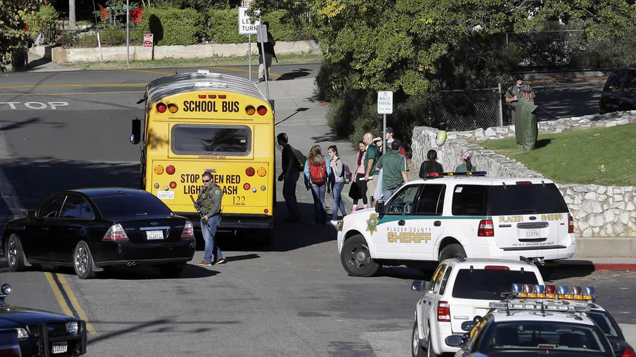 Placer High School students board a bus as law enforcement officers stand guard in Auburn, Calif., Friday, Oct. 24, 2014. (AP Photo/Rich Pedroncelli)