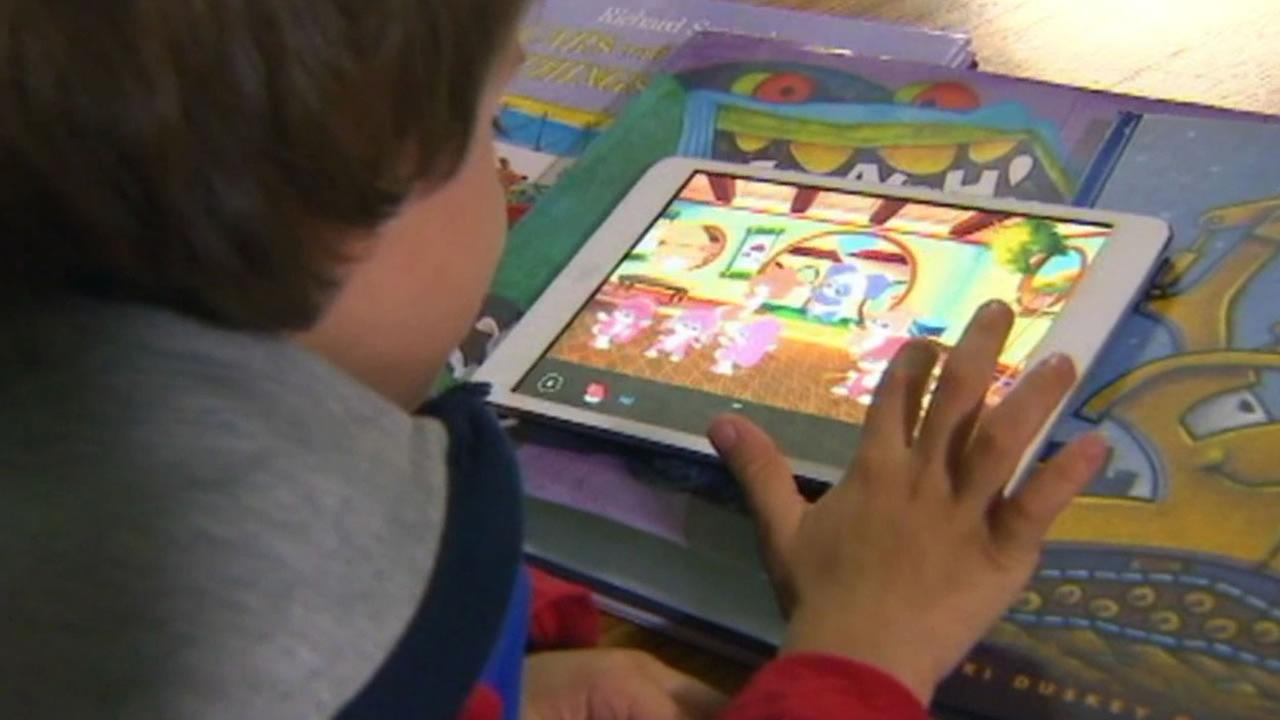 A child playing with an electronic reader or e-book.