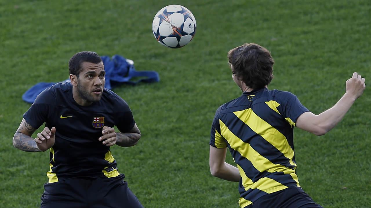 FC Barcelonas Dani Alves, left, heads the ball towards a team mate during a training session at the Vicente Calderon stadium in Madrid, Spain, Tuesday, April 8, 2014. (AP Photo/Andres Kudacki)