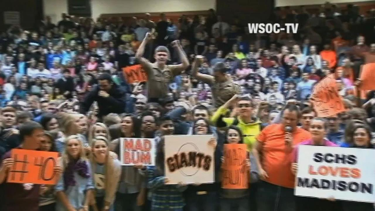 crowd at high school holding signs