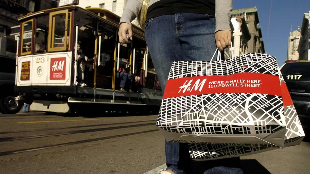 Holding H&M bags, Lilly Jan waits for a taxi after shopping at the stores San Francisco location, Nov. 19, 2005. (AP Photo/Noah Berger)