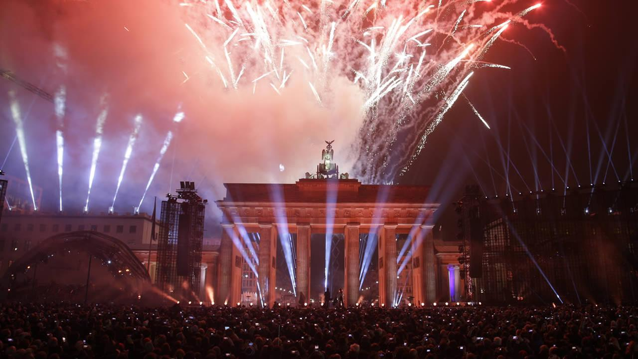 Fireworks explode behind Brandenburg Gate during the central event commemorating the fall of the wall in Berlin, Germany, Sunday, Nov. 9, 2014. (AP Photo/Michael Sohn)