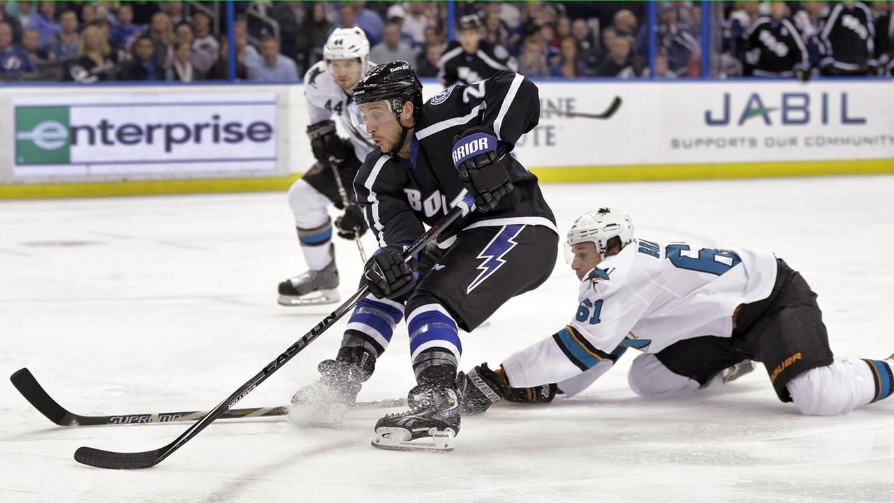 ampa Bay Lightning right wing Ryan Callahan (24) cuts around San Jose Sharks defensemen Justin Braun (61) and Marc-Edouard Vlasic (44) as he goes to the goal.