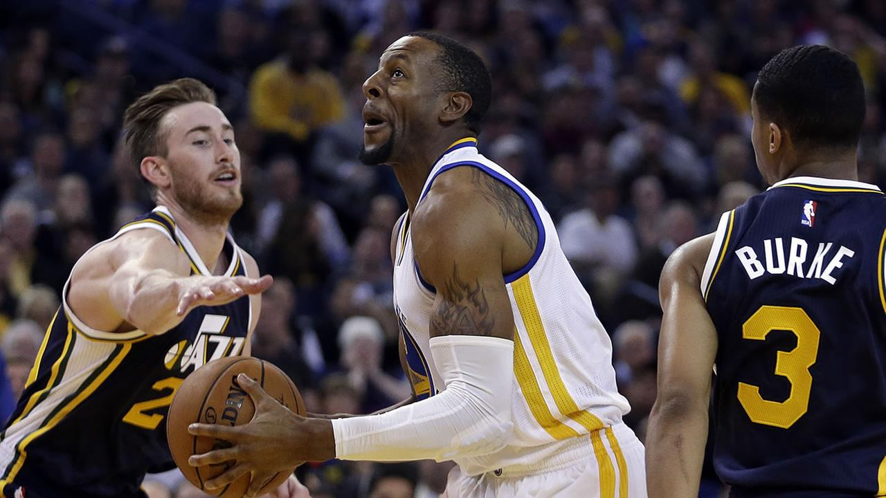 Golden State Warriors Andre Iguodala, center, drives the ball between Utah Jazz forward Gordon Hayward, left, and Trey Burke