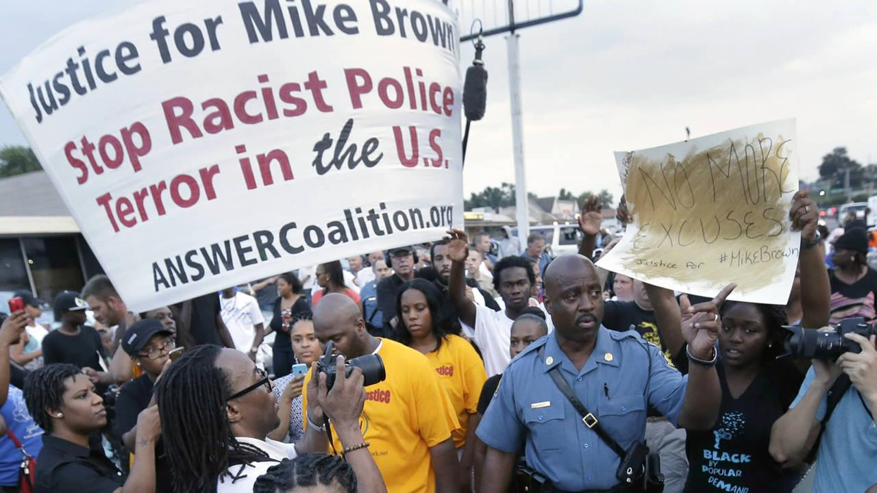Capt. Ron Johnson, center right, walks among people protesting the police shooting death of Michael Brown in Ferguson, Mo. on Aug, 16, 2014 (AP Photo/Charlie Riedel, File)