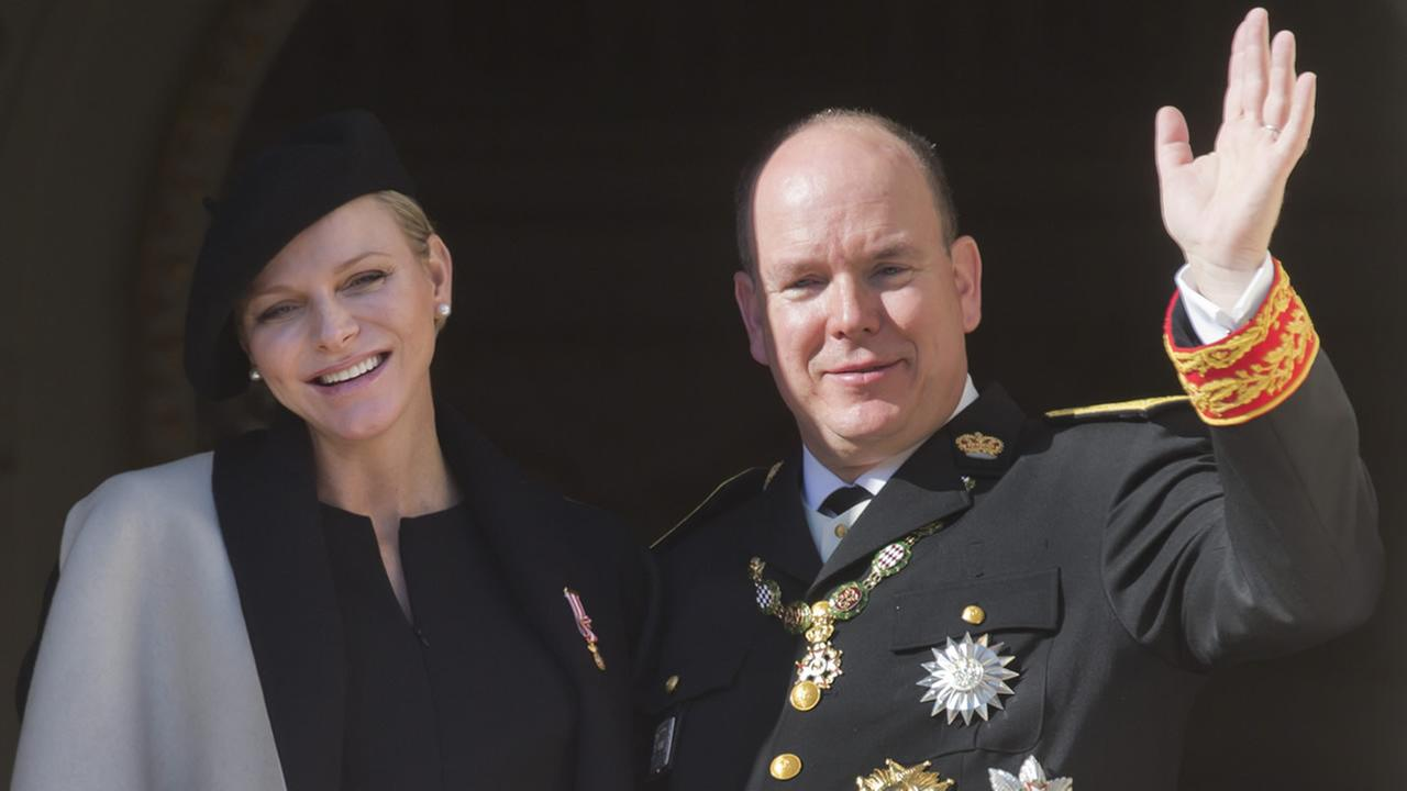 Prince Albert II of Monaco with his wife Princess Charlene look out from the Monaco palace to the Monacos national day ceremony, Nov. 19, 2014. (AP Photo/Lionel Cironneau)