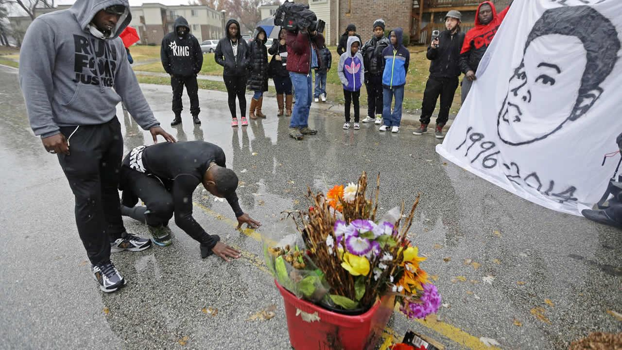 Ray Mills and Londrelle Hall pause before a memorial in the middle of a street Sunday, Nov. 23, 2014, more than three months after Michael Brown was shot and killed. (AP Photo)