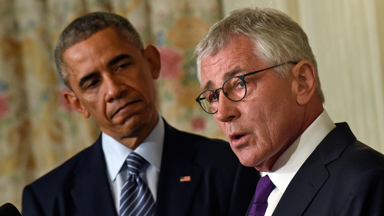 President Obama, left, listens as Defense Secretary Chuck Hagel, right, talks about his resignation during an event in the State Dining Room of the White House in Washington.