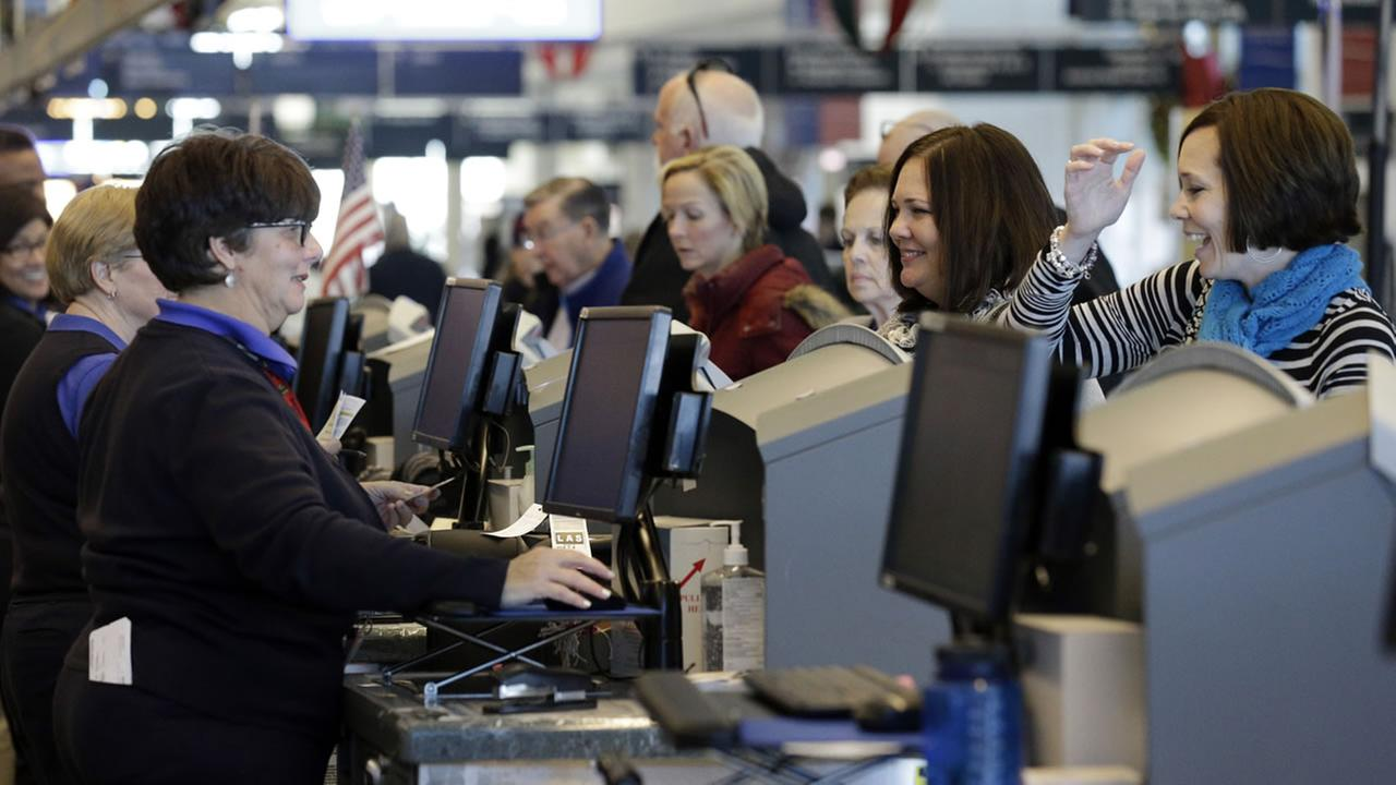 Travelers check tickets and their bags with check in counters at Midway International Airport, Friday, Nov. 21, 2014., in Chicago.(AP Photo/Nam Y. Huh)