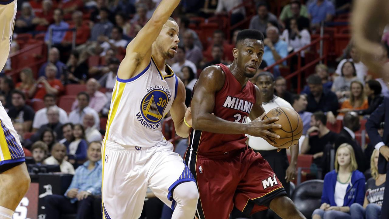 Miami Heat guard Norris Cole, right, drives to the basket as Golden State Warriors guard Stephen Curry (30) defends in the first half of an NBA basketball game.